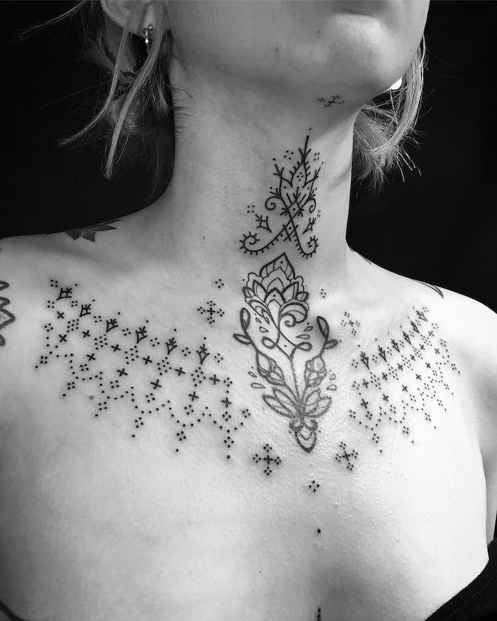 symmetrical lotus flower and dots tattoo, chest tattoos for women, black top and background