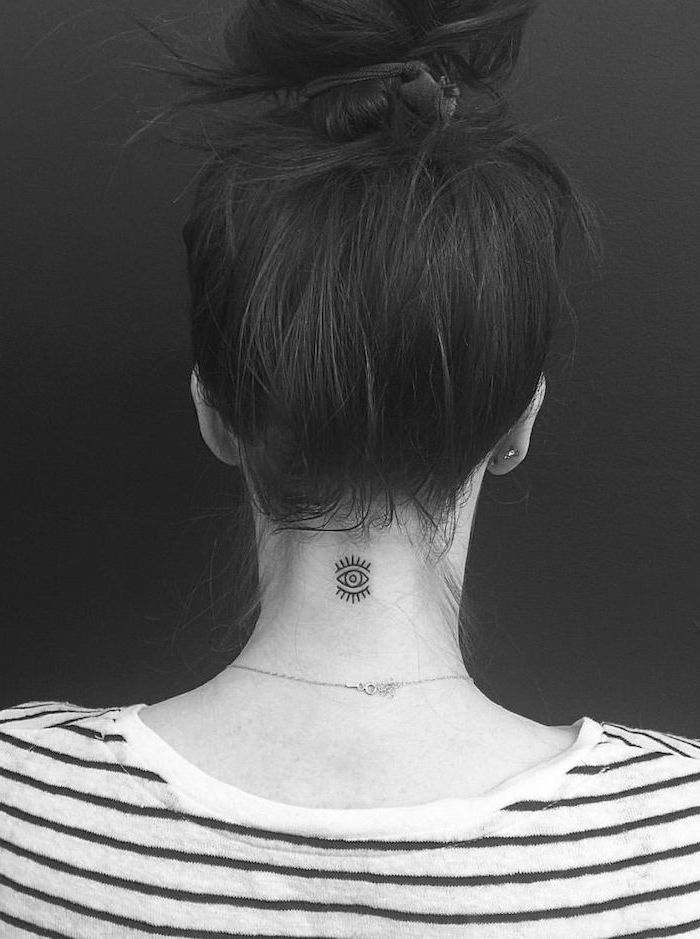 tattoos for women with a meaning, black hair in a bun, evil eye tattoo on the neck, black and white striped shirt