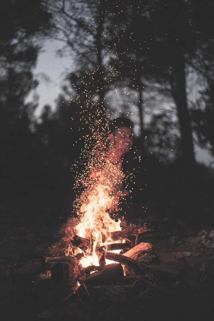man sitting next to a fire, inspirational wallpapers, tall trees, grey skies