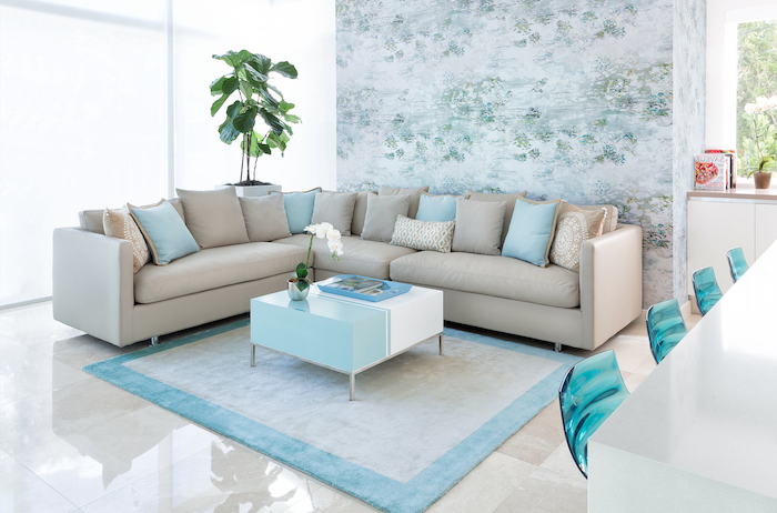 floral wallpaper, blue rug, blue and white coffee table, accent wall colors, beige sofa with blue throw pillows