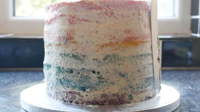 frosting spread around the cake, silver cake stand, unicorn birthday cake, blue countertop