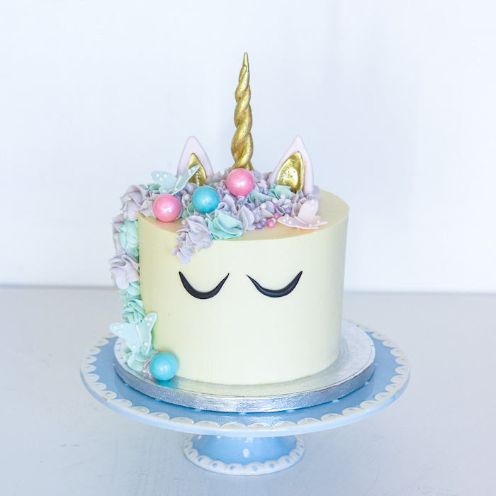 rainbow unicorn cake, blue cake stand, purple and blue roses on white fondant, gold horn and ears