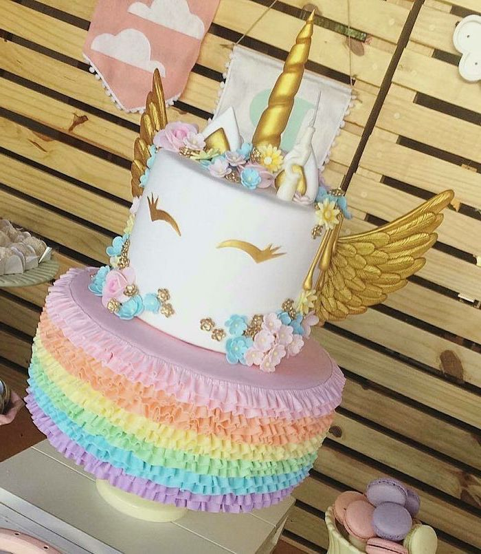 gold horn and wings, unicorn cupcake cake, rainbow coloured roses first layer, pink and blue flowers