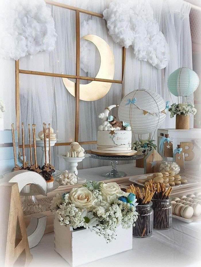 white tulle with fairy lights, baby shower themes for boys, flowers in a wooden crate, cake macaroons and cake pops on the table