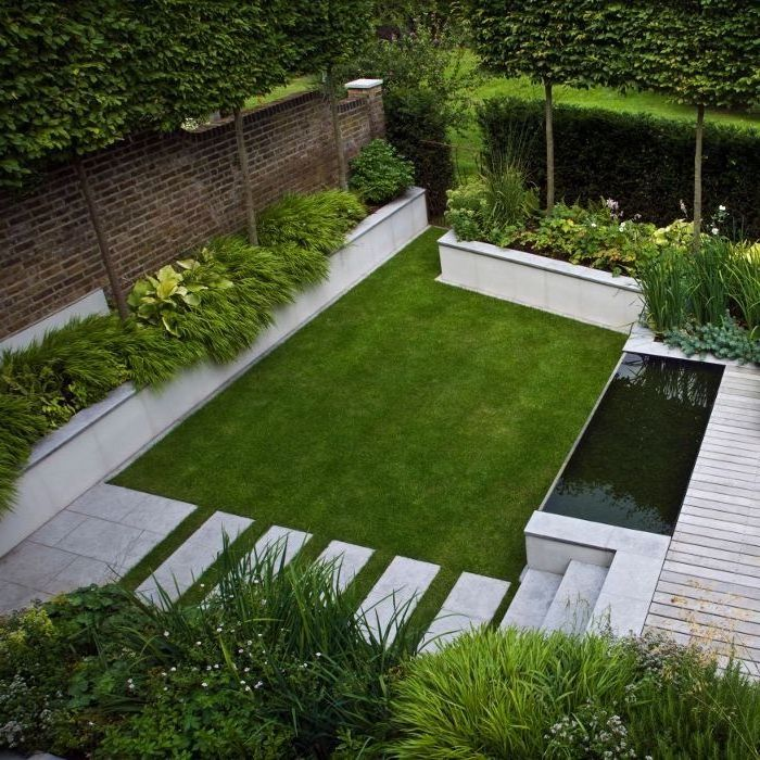 large patch of grass, rock landscaping ides, patches of bushes and grass, hedges and tall trees