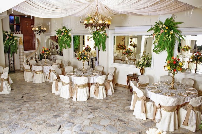 hanging fabric and lights from the ceiling, hanging flower arrangements on the wall and in vases, wedding reception decorations