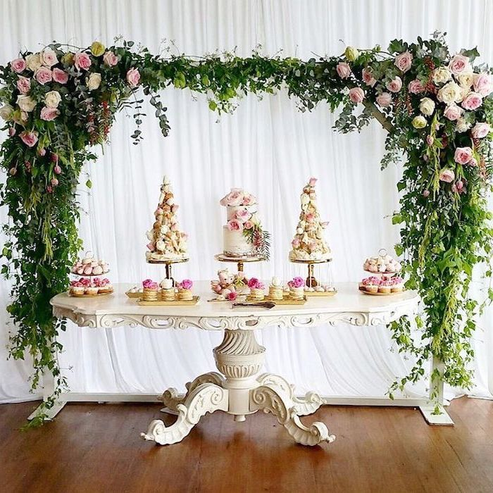 pink white and yellow flower arch, white antique table, cake and macaroon dessert on the table, wedding table decorations