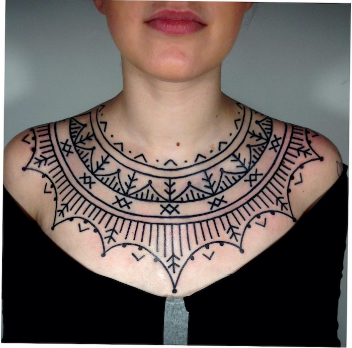 black top, blue background, rose chest tattoo, symmetrical geometrical shapes tattoo