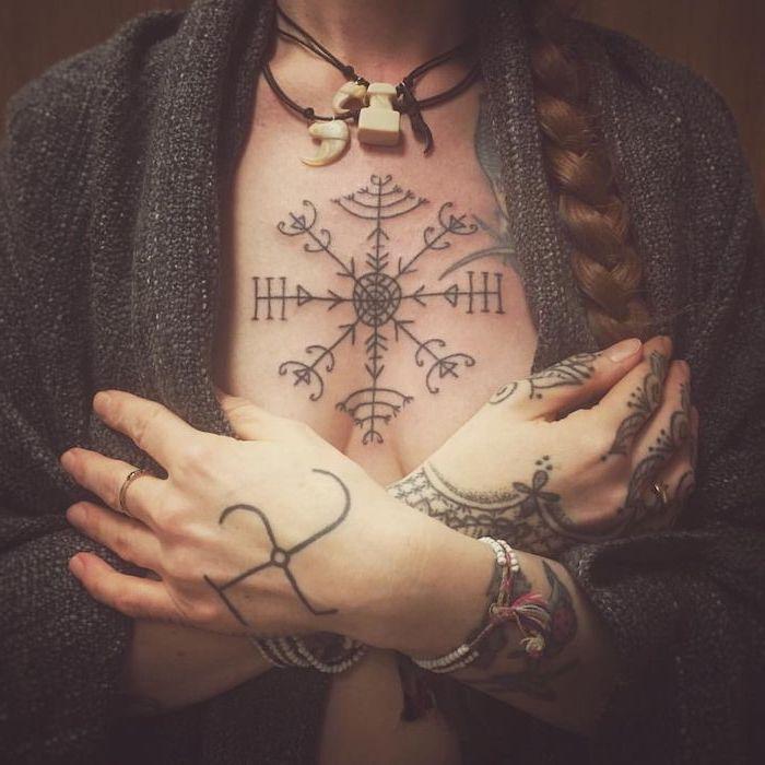 tattoos for women, dark grey cardigan, symmetrical tattoo with arrows, braided brown hair