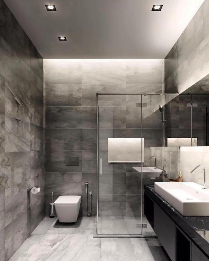 grey tiled floor and walls, glass shower door, how to decorate a bathroom, floating black cabinets