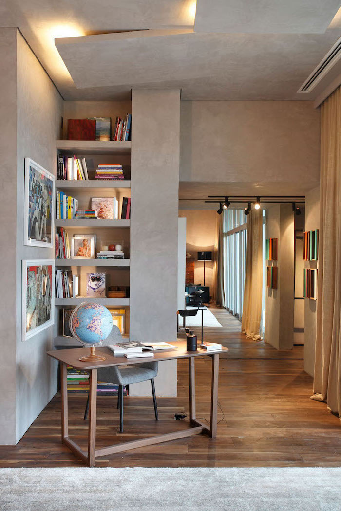 grey walls and rug, wooden desk, bookcase with lots of books, grey chair, desk ideas