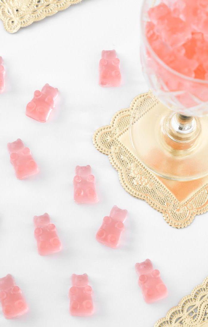 wine glass, pink gummy bears, bachelorette games, golden coaster, white table