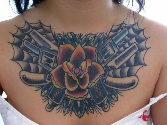 small chest tattoos, large red and yellow rose with guns and webs, white top and background