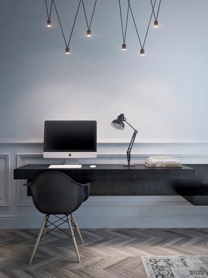 grey walls, hanging chandelier, black desk and chair, wooden floor with a rug, desk ideas