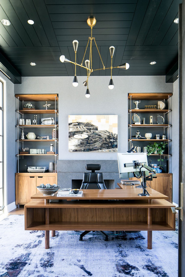 blue rug on the floor, wooden desk with black leather armchair, office decor ideas, wooden bookcases
