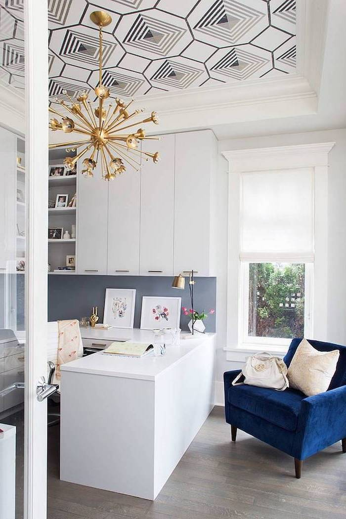 navy blue velvet armchair, small home office ideas, metal golden hanging chandelier, white desk and cabinets