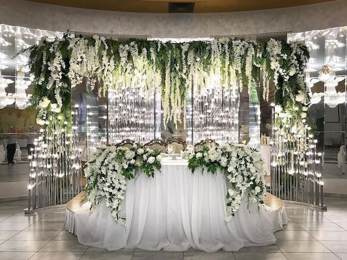 white tulle on the table, hanging white and green flower arrangements on the ceiling, wedding ideas for summer