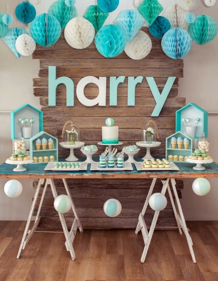 white blue and turquoise paper flowers hanging, baby shower centerpieces boy, cake and sweets on the table