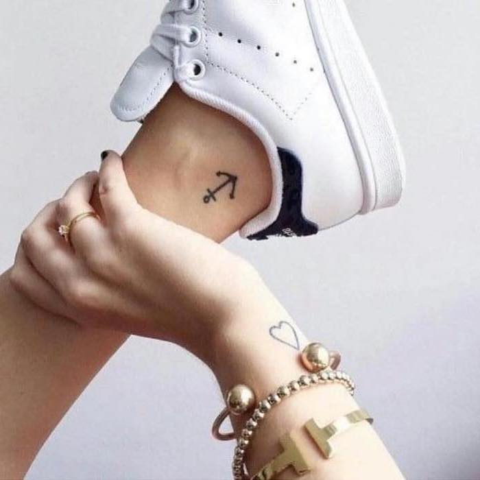 anchor tattoo on the ankle, heart tattoo on the wrist, small tattoo ideas for women, golden jewellery on the hand