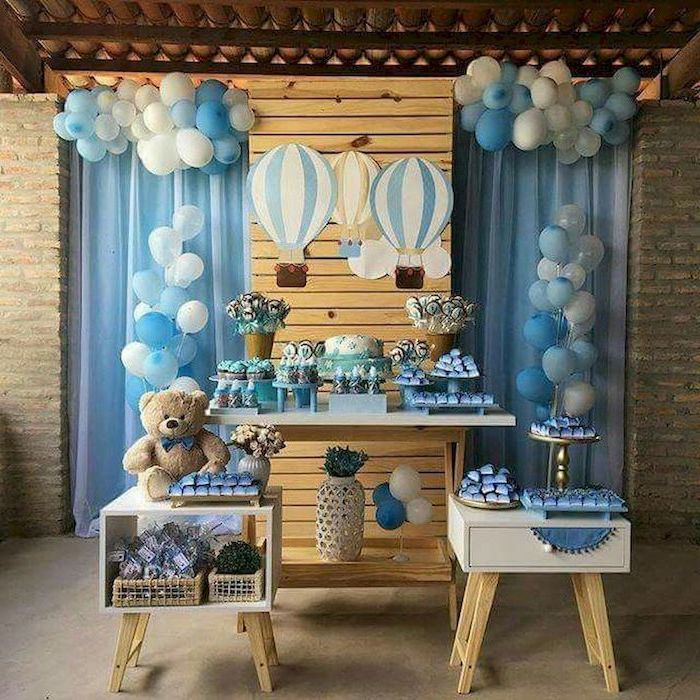 baby shower centerpieces boy, white and blue balloons, cake and sweets on the table, plush teddy bear