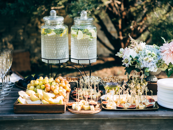 lemonade jars on a stand, grapes and apples in a tray, small bites on trays, flower bouquet in a vase, wedding table decorations
