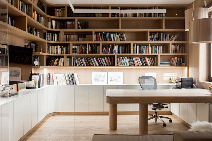 large wooden bookcase with many shelves and cupboards, wooden desk with mesh black chair, home office decor