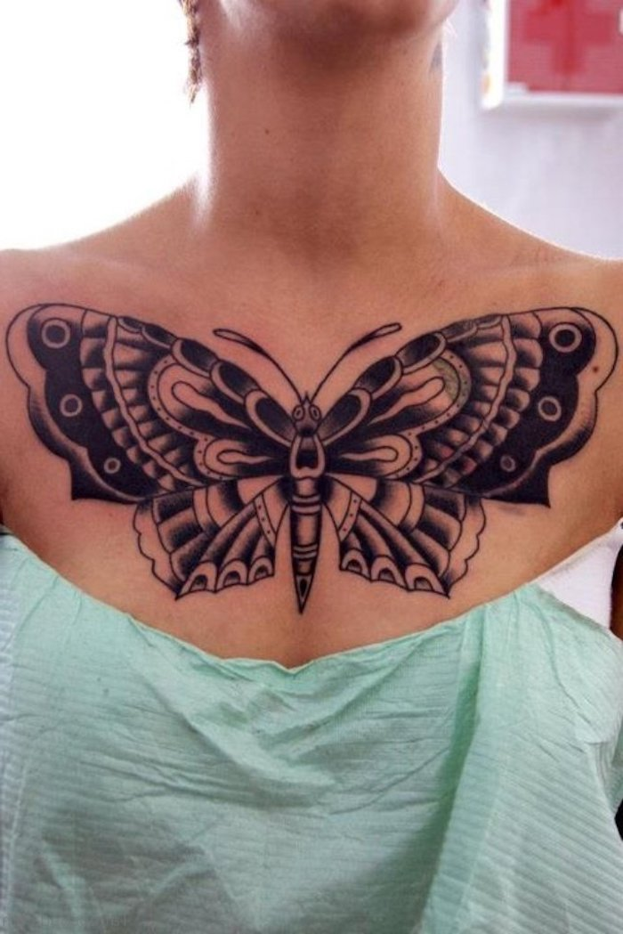 tattoos for women with meaning, large black butterfly, green paper, white top and background, tattoo designs for womens chest