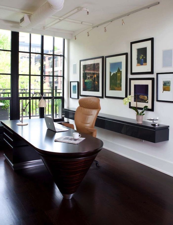 large dark wooden desk, brown leather chair, small home office ideas, black bookshelf, photos on the wall
