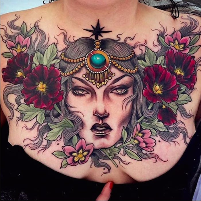 black top, large pink flowers and green leaves, large female face, tattoos for women with meaning
