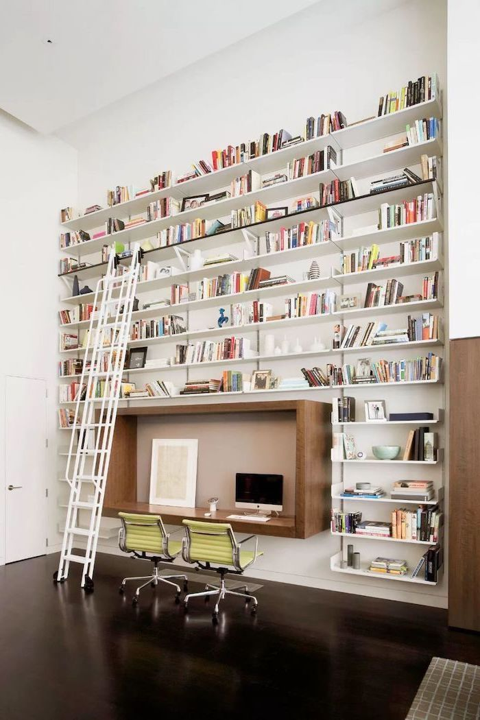 multiple bookshelves with books, sliding ladder, wooden desk, green chairs, home office decor