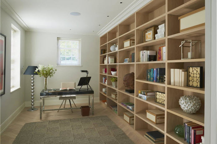 large bookcase, black metal desk, white chair, standing lamp, cute office decor, beige rug on a wooden floor