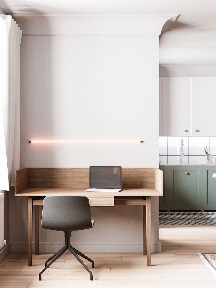 white walls, wooden desk with a laptop, led light above the desk, office design ideas, black chair