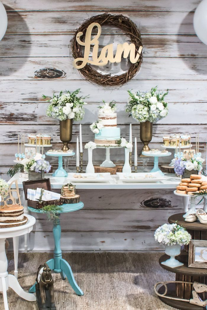 flower bouquets in vases, cake and sweets on the table, baby shower themes for boys, wooden backdrop