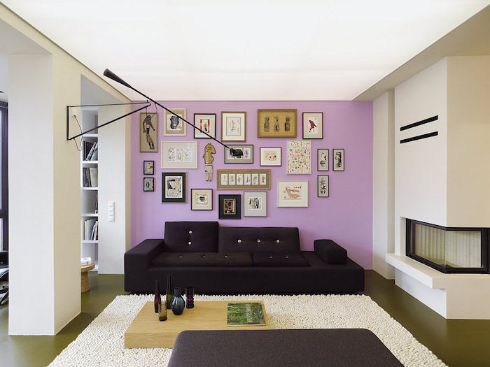 light purple wall with lots of photos and pictures, black sofa, wall painting ideas, wooden coffee table
