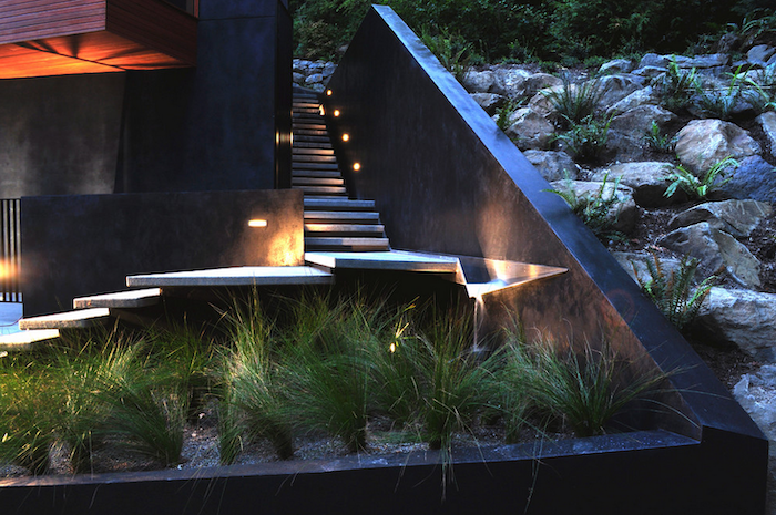 minimalistic staircase with lights, small patch of bushes, small front yard landscaping ideas, large rocks