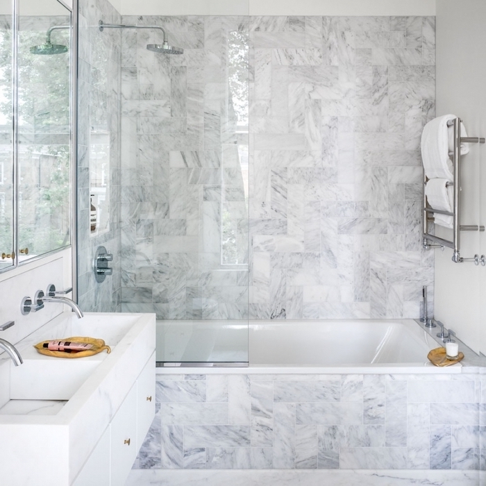 marble tiled walls and bathtub, glass shower door, small bathroom layout, floating white cabinets and sink