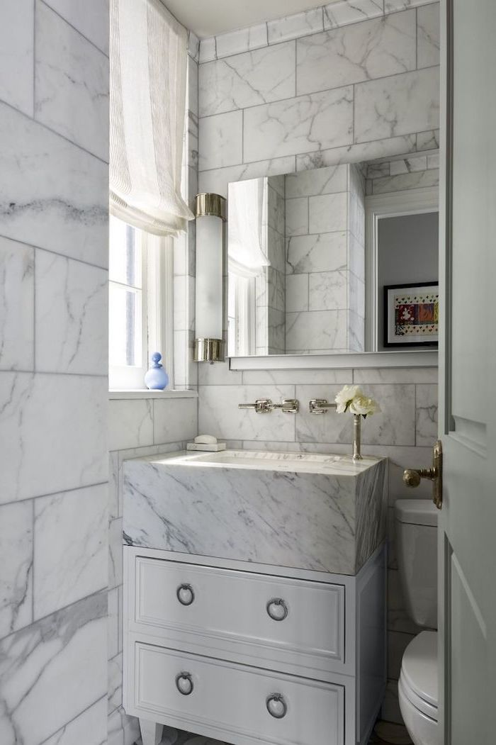 marble tiled walls and sink, white drawers under the sink, large mirror, small bathroom layout
