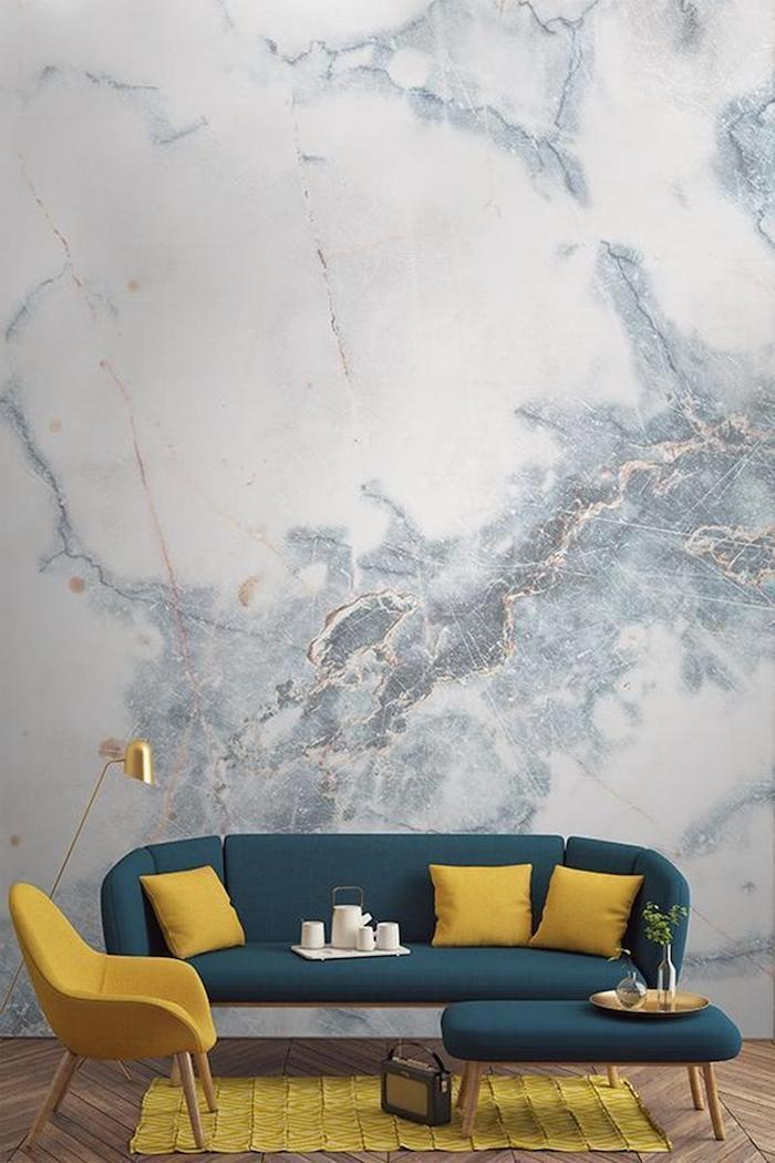 blue marble wallpaper, wall painting ideas, blue sofa with yellow throw pillows, yellow armchair and rug