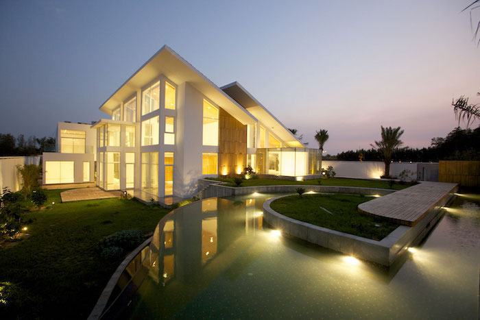 futuristic house, large grass patch, backyard landscaping ideas, large pool, palm trees, patches of small bushes with lights