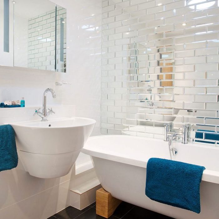 small bathroom layout, mirror tiled wall, floating white sink and bathtub, small mirror, white wall