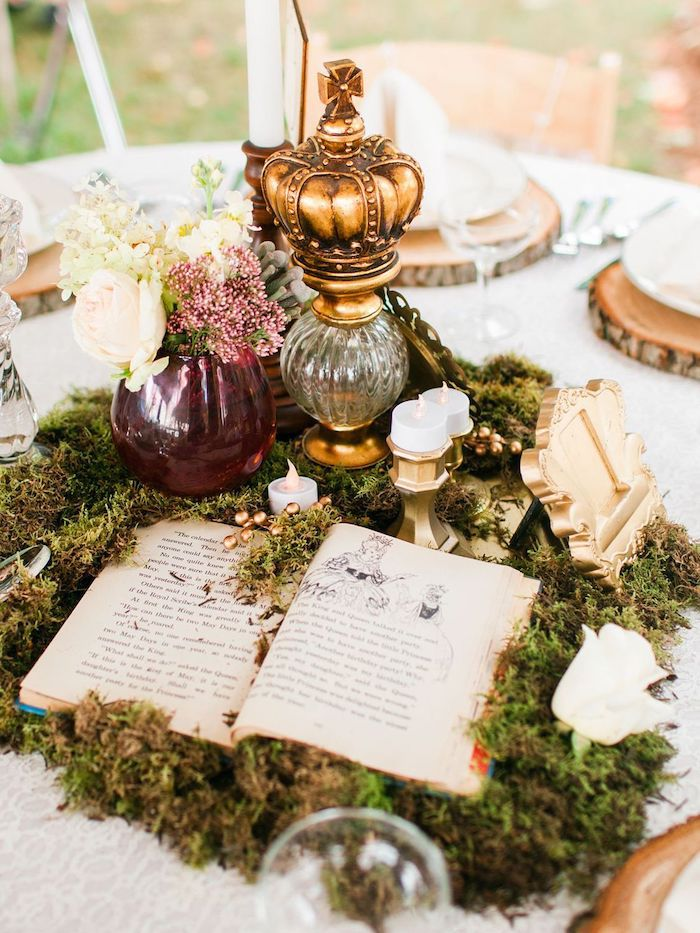 centrepiece with moss and book, white and pink flower bouquet, glass goblet with a crown, outdoor wedding ideas