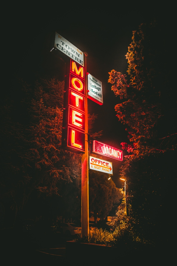 large motel sign, pretty iphone wallpaper, neon signs, tall trees and a pathway