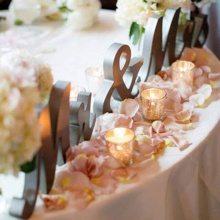 mr and mrs metal sign, rose petals on the table with candles, flower bouquets, wedding table settings
