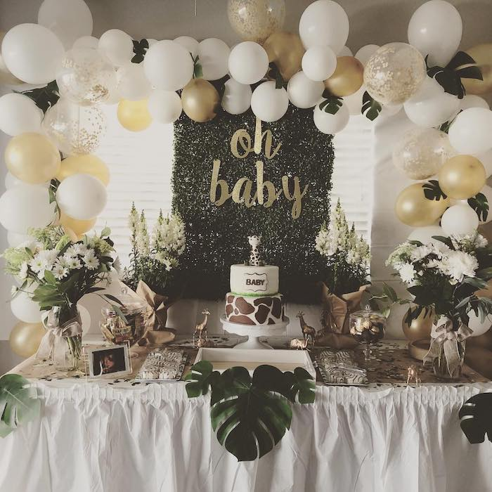 white and gold balloons arch, cake and sweets on the table, baby shower theme ideas, flower bouquets in vases