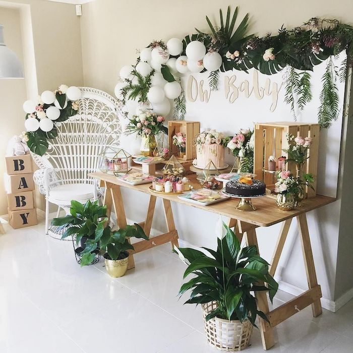 greenery and white balloons hanging, baby shower themes for boys, wooden crates with flowers, sweets on the table