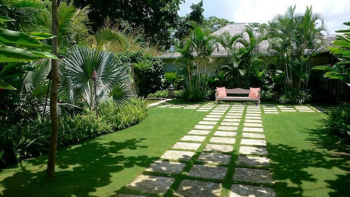 geometrical stone tiles in the grass, tall palm trees, landscape lighting ideas, patches of bushes