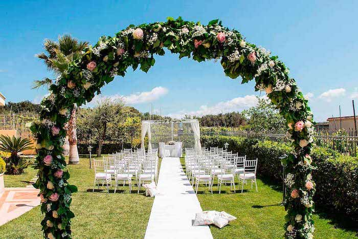 pink and yellow roses arch, white chairs and tulle next to the aisle, palm trees, wedding decoration ideas