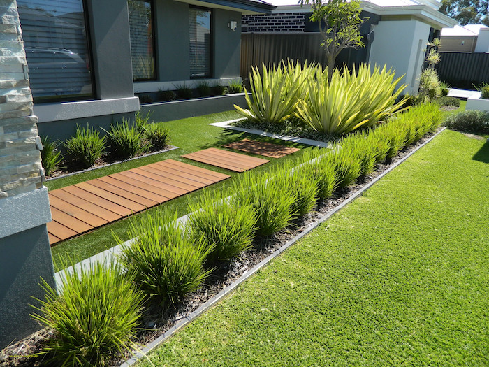 patch of grass, small backyard landscaping ideas, wooden pathway, small symmetrical bushes,
