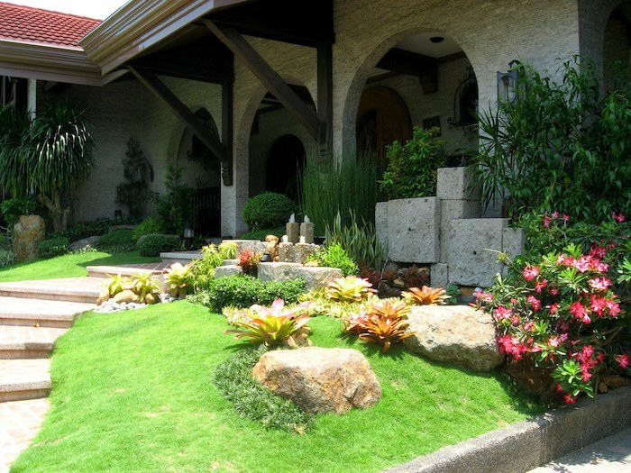 tiled pathway, grass patch with rocks and flowers, pool landscaping ideas, flower beds, large bushes