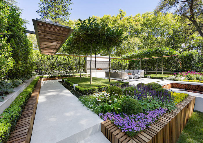 flower beds, small hedges, pool landscaping ideas, tall trees, pink and purple flowers